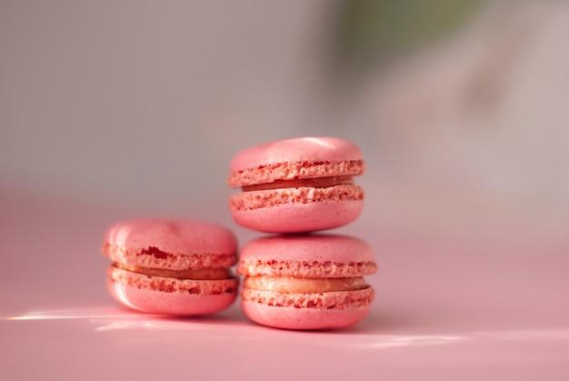 Różowe Kolorowe Makaroniki Smaczne Francuskie Ciasteczka Z Błyszczącymi Promieniami Słońca Oświetlają Róż Premium Zdjęcia