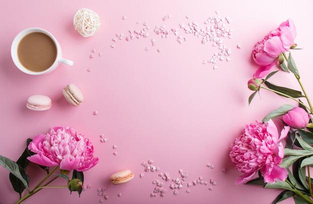 Różowe kwiaty piwonii i filiżankę kawy na różowy pastel. Premium Zdjęcia