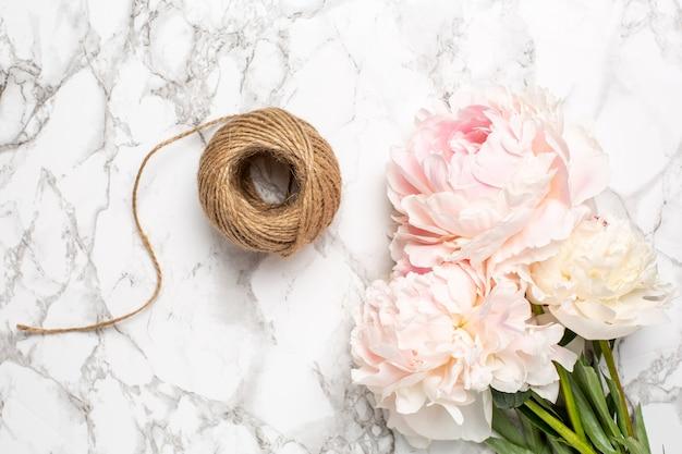 Różowe kwiaty piwonii i sznurka na marmurowej powierzchni. przedmiot świąteczny i letni. Premium Zdjęcia