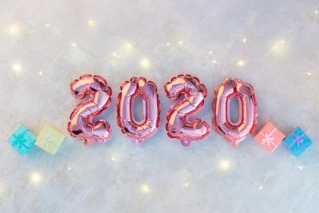 Różowe liczby 2020 na białym betonie, girlanda gwiazd mieniąca się kolorowymi światłami. Premium Zdjęcia