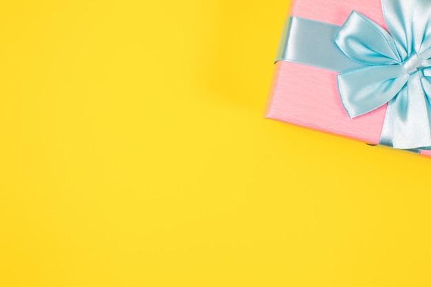 Różowe Pudełko Związane Z Niebieską Wstążką Z Kokardą Na Górze Na żółtym Tle. Skopiuj Miejsce Na Tekst. Minimalne Płaskie Ułożenie. Premium Zdjęcia
