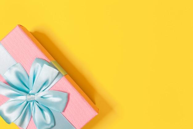 Różowe Pudełko Związane Z Niebieską Wstążką Z Kokardą Na Górze Na żółtym Tle. Skopiuj Miejsce. Premium Zdjęcia