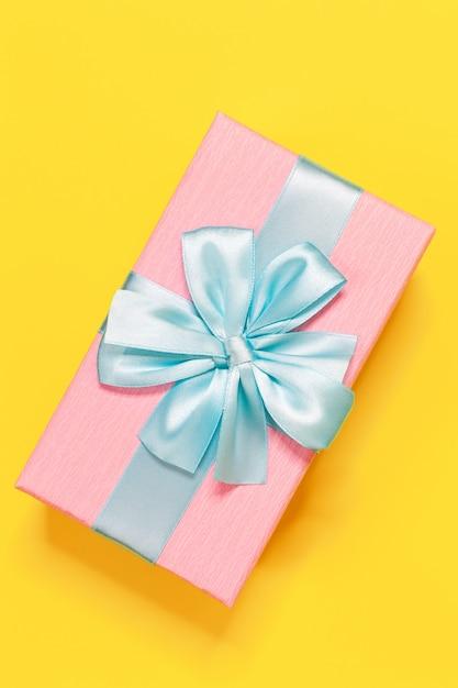 Różowe Pudełko Związane Z Niebieską Wstążką Z Kokardą Na Górze Na żółtym Tle. Premium Zdjęcia