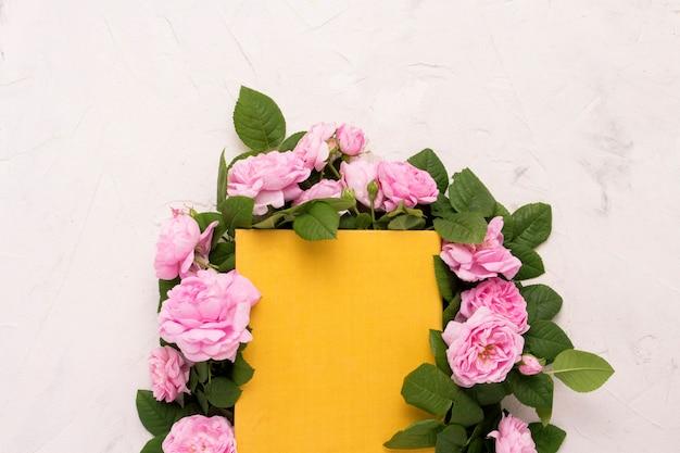 Różowe Róże Są Wyłożone Wokół Książki Z żółtą Okładką Premium Zdjęcia