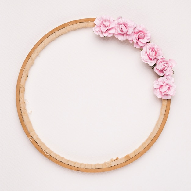 Różowe róże zdobione na okrągłej drewnianej ramie na białym tle Darmowe Zdjęcia