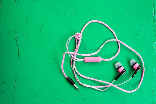 Różowe Słuchawki Stereo Na Drewnianej Zieleni Premium Zdjęcia