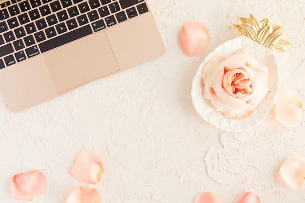 Różowego złota laptop na biurowym stole biurku z róż kwiatami i płatkami na białym z betonową teksturą Premium Zdjęcia
