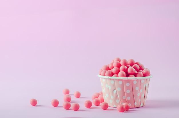 Różowi Cukierki W Różowej Papierowej Filiżance Z Białym Polki Kropki Wzorem Na Różowym Tle Premium Zdjęcia