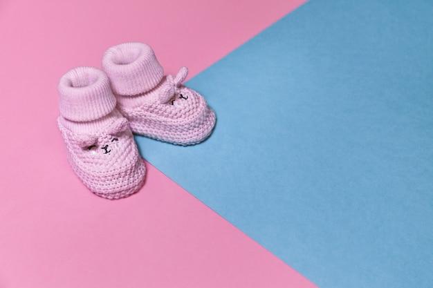 Różowi nowonarodzeni trykotowi buty na pastelowym papierowym tle z kopii przestrzenią Premium Zdjęcia