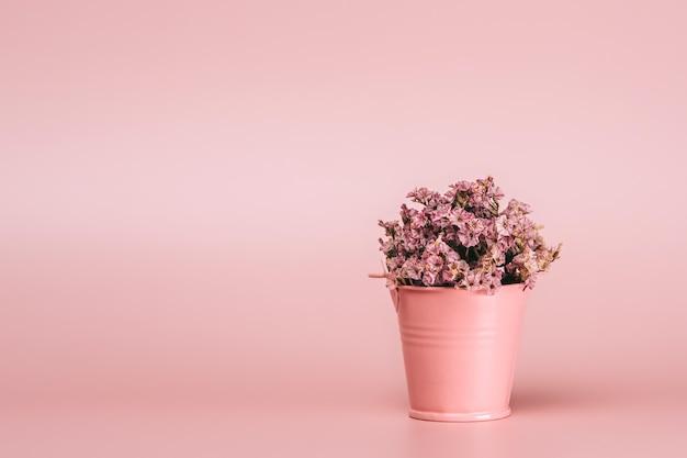 Różowy Kosz Metalowy Z Naturalnymi Kwiatami Na Różowej ścianie. Premium Zdjęcia