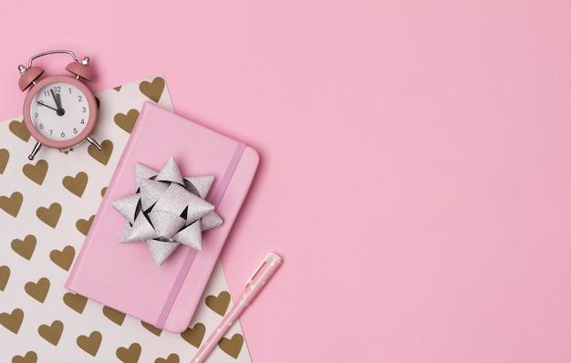 Różowy notatnik z budzikiem, łuk i długopis na kreatywnym tle Premium Zdjęcia