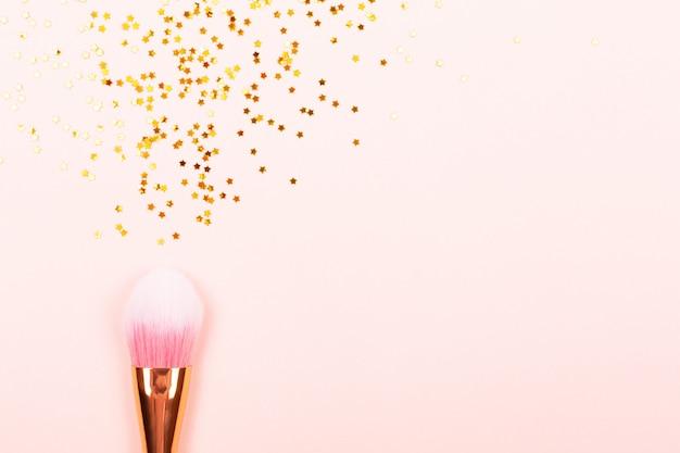Różowy pędzel do makijażu i konfetti Premium Zdjęcia