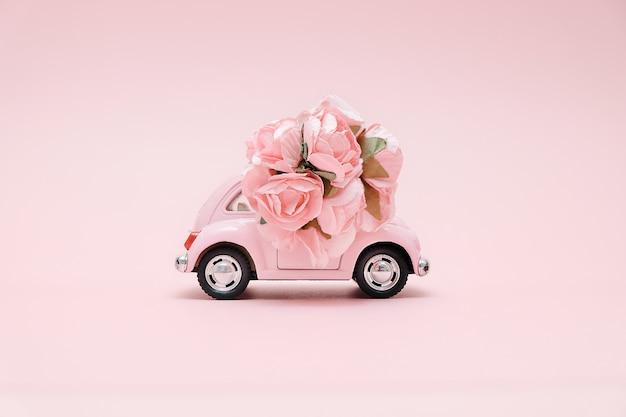 Różowy retro zabawkarski samochód dostarcza bukiet kwiaty Premium Zdjęcia