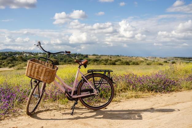 Różowy Rower Z Koszem W Pięknym Polu Pełnym Kwiatów Premium Zdjęcia