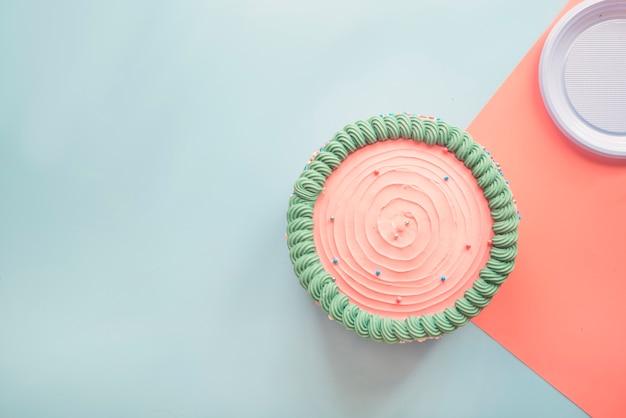 Różowy Tort Na Błękita światła Tle Premium Zdjęcia