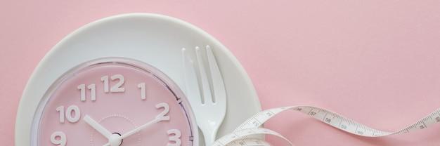 Różowy zegar na białym talerzu Premium Zdjęcia