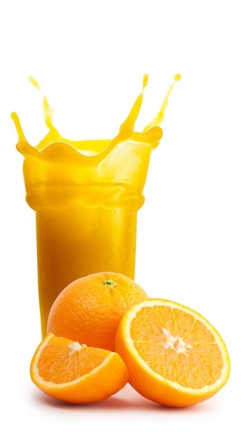 Rozpryskaj Szklankę Soku Pomarańczowego Z Ciętymi Pomarańczami Premium Zdjęcia