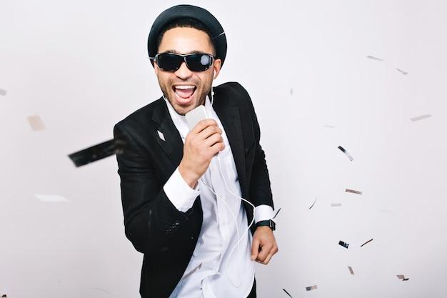 Rozrywka, świętowanie Imprezy Karaoke Podekscytowanego Przystojnego Faceta W Czarnych Okularach Przeciwsłonecznych. Modny Wygląd, śpiew, Muzyka, Radość, Wyrażanie Pozytywności, Radość. Darmowe Zdjęcia