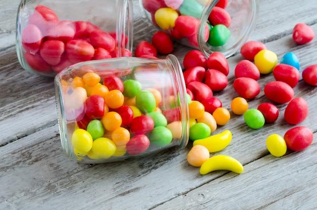 Rozrzucone Cukierki W Pobliżu Słoika Kolorowych Słodyczy Premium Zdjęcia