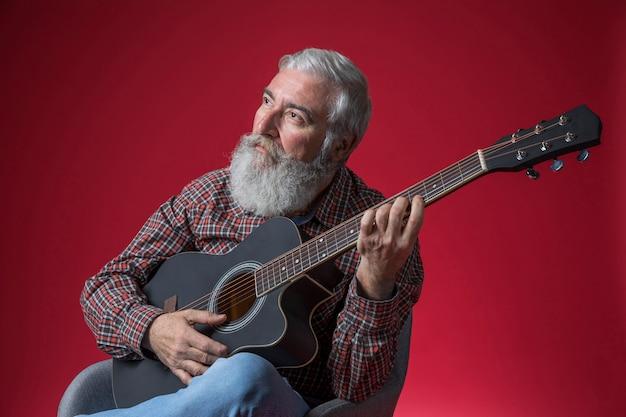 Rozważany starszy mężczyzna gra na gitarze na czerwonym tle Darmowe Zdjęcia