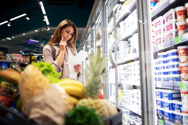 Rozważna Kobieta W Supermarkecie Trzyma Listę I Czyta Artykuły, Które Zamierza Kupić Darmowe Zdjęcia
