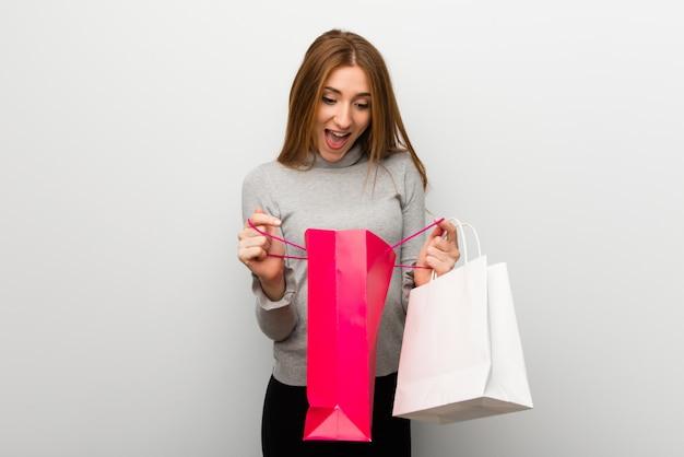 Ruda dziewczyna nad białą ścianą zaskoczona, trzymając wiele toreb na zakupy Premium Zdjęcia