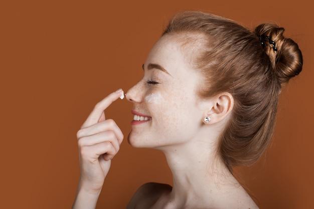 Ruda Kobieta Z Piegami Nakładająca Krem Na Twarz I Uśmiechająca Się Z Nagimi Ramionami Na Brązowej ścianie Z Wolną Przestrzenią Premium Zdjęcia