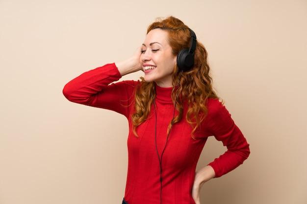 Rude Kobiety Z Golfem Sweter Słuchania Muzyki W Słuchawkach Premium Zdjęcia