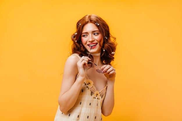 Rudowłosa Kobieta W Kraciastej Sukni Uśmiecha Się I Gryzie Kajdany Okularów Przeciwsłonecznych Na żółtym Tle. Darmowe Zdjęcia