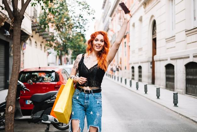 Rudowłosa kobieta wędrując taksówką Darmowe Zdjęcia