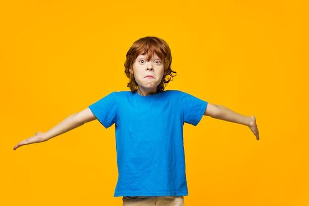 Rudowłosy Chłopiec Niebieski T-shirt Z żółtymi Piegami W Tle Wzrusza Ze Zdziwienia Rękami Na Boki Premium Zdjęcia