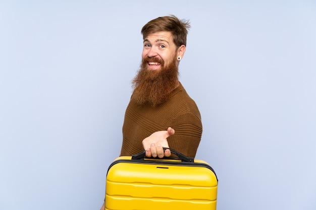 Rudy mężczyzna z długą brodą, trzymając walizkę, bardzo się uśmiecha Premium Zdjęcia