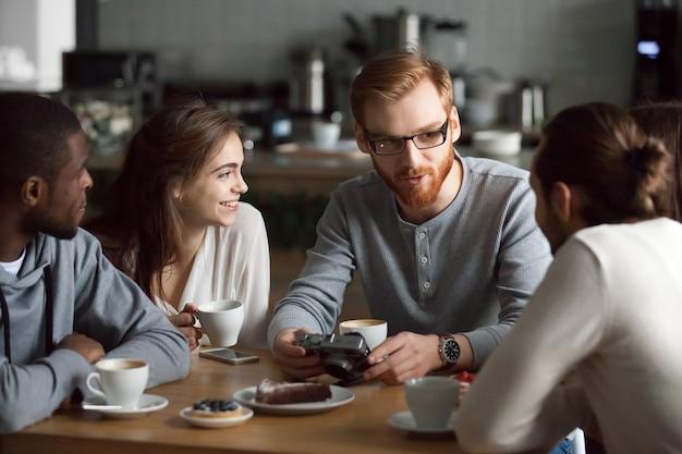 Rudzielec facet pokazuje kamer fotografie różnorodni przyjaciele w kawiarni Darmowe Zdjęcia