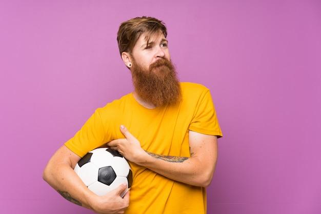 Rudzielec mężczyzna trzyma piłki nożnej piłkę nad odosobnioną purpurą ścienny przyglądający up z długą brodą podczas gdy ono uśmiecha się Premium Zdjęcia
