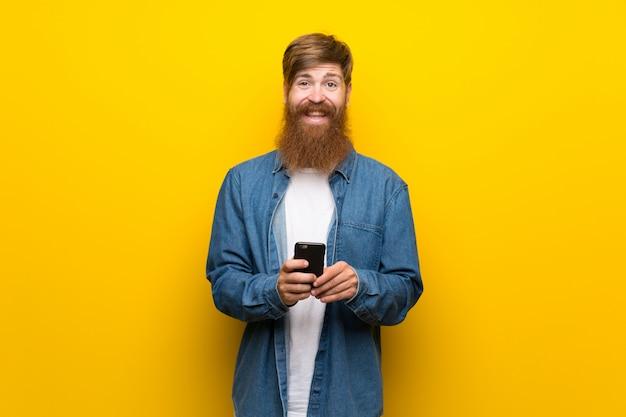 Rudzielec mężczyzna z długą brodą nad kolor żółty ścianą używać telefon komórkowego Premium Zdjęcia