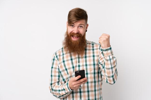 Rudzielec Mężczyzna Z Długą Brodą Nad Odosobnioną Biel ścianą Z Telefonem W Zwycięstwo Pozycji Premium Zdjęcia