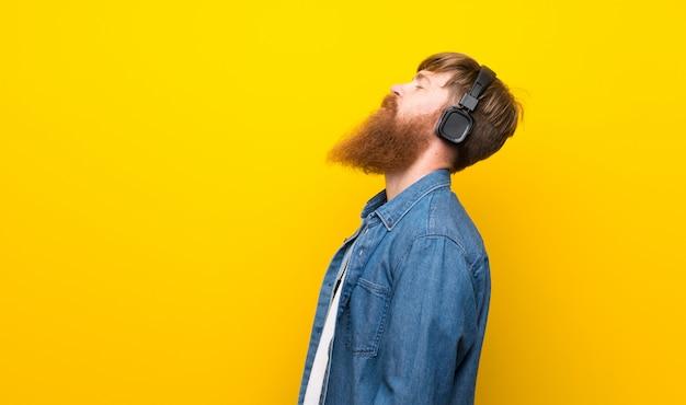Rudzielec Mężczyzna Z Długą Brodą Nad Odosobnioną Kolor żółty ścianą Słucha Muzyka Z Hełmofonami Premium Zdjęcia