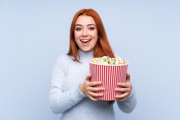 Rudzielec Nastolatka Dziewczyna Nad Odosobnioną Błękit ścianą Trzyma Dużego Wiadro Popcorns Premium Zdjęcia
