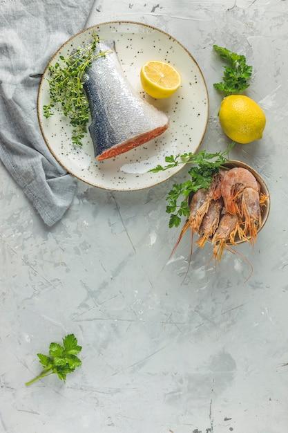 Ryba Pstrągowa Otoczona Natką Pietruszki, Cytryny, Krewetek, Krewetek Na Talerzu Ceramicznym Premium Zdjęcia