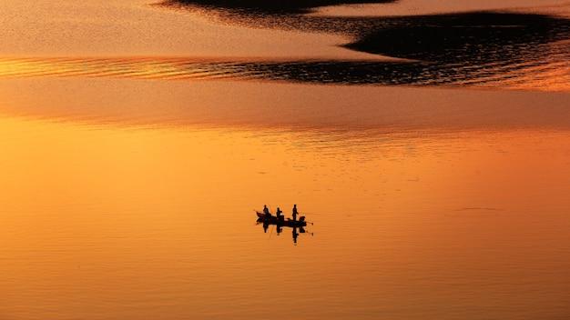 Rybak łowiący Z łodzi Na Jeziorze O Zachodzie Słońca Premium Zdjęcia