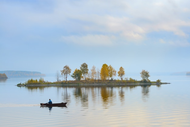 Rybak Pływa Wokół Wyspy Na Jeziorze Premium Zdjęcia