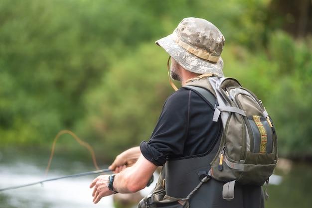 Rybak Połowów Na Rzece, Trzymając Wędkę. Premium Zdjęcia