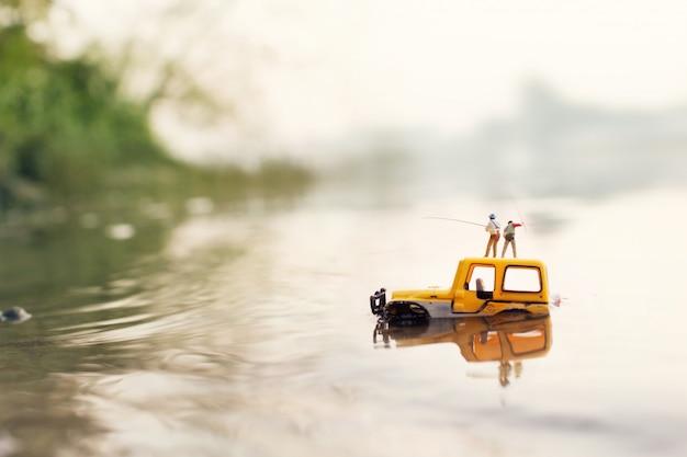 Rybak Trzymający Wędkę Do Połowu Ryb (miniatura, Model Zabawkowy) Premium Zdjęcia