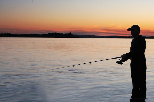 Rybak Wędkarski Z Wędką Spinningową Na Brzegu Rzeki O Zachodzie Słońca Mglisty Premium Zdjęcia