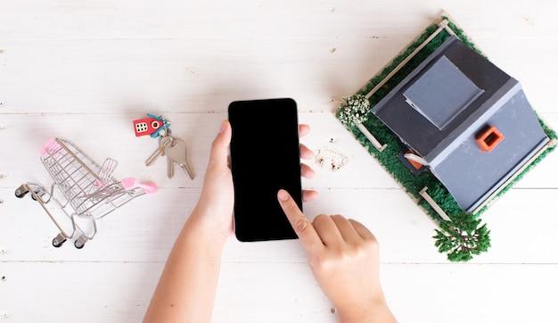 Rynek nieruchomości z kluczami do domu, koszykiem i telefonem Darmowe Zdjęcia