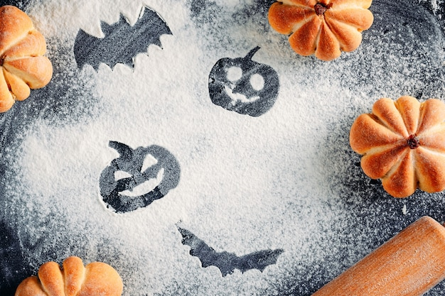 Rysowanie Dekoracji Halloween Na Tle Mąki, Ciastek W Kształcie Dyni I Wałka Do Ciasta. Koncepcja Gotowania Halloween Premium Zdjęcia