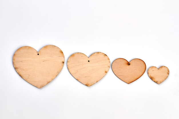 Rząd Drewnianych Wycinanek W Kształcie Serca. Cztery Drewniane Serca Na Białym Tle. Ręcznie Robione Dekoracje Na Walentynki. Premium Zdjęcia