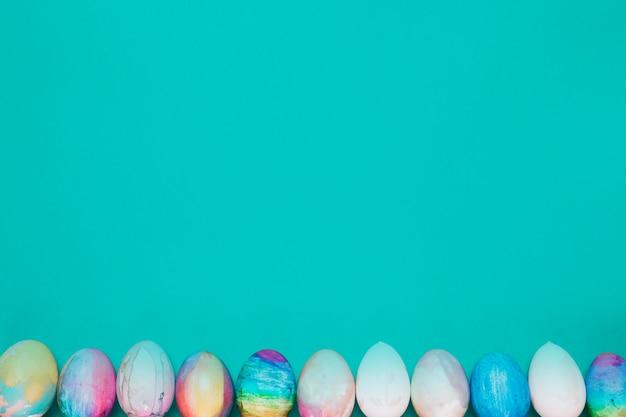 Rząd Malujący Easter Jajka Na Dnie Turkusowy Tło Darmowe Zdjęcia