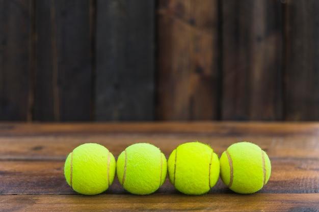 Rząd zielone tenisowe piłki na drewnianym textured tle Darmowe Zdjęcia
