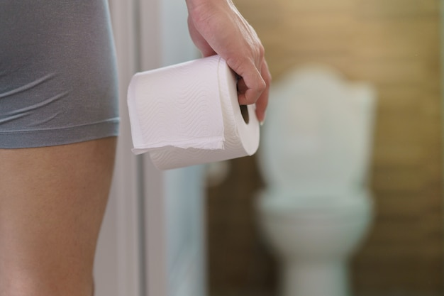Rzadki Widok Człowieka Posiadającego Rolkę Papieru Toaletowego Przed Toaletą. Premium Zdjęcia